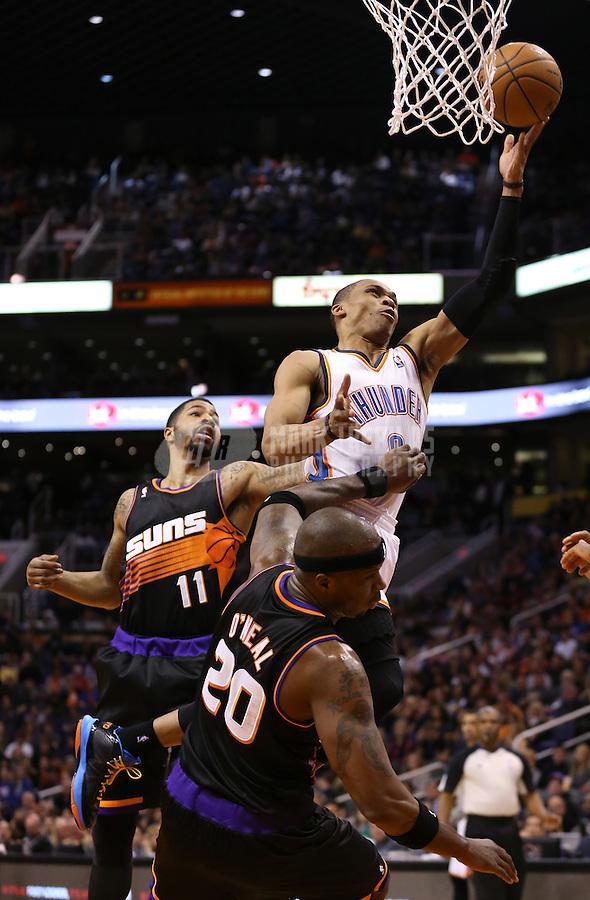Feb. 10, 2013; Phoenix, AZ, USA: Oklahoma City Thunder guard Russell Westbrook (0) drives to the basket in the second quarter past Phoenix Suns forward Markieff Morris (11) at the US Airways Center. Mandatory Credit: Mark J. Rebilas-