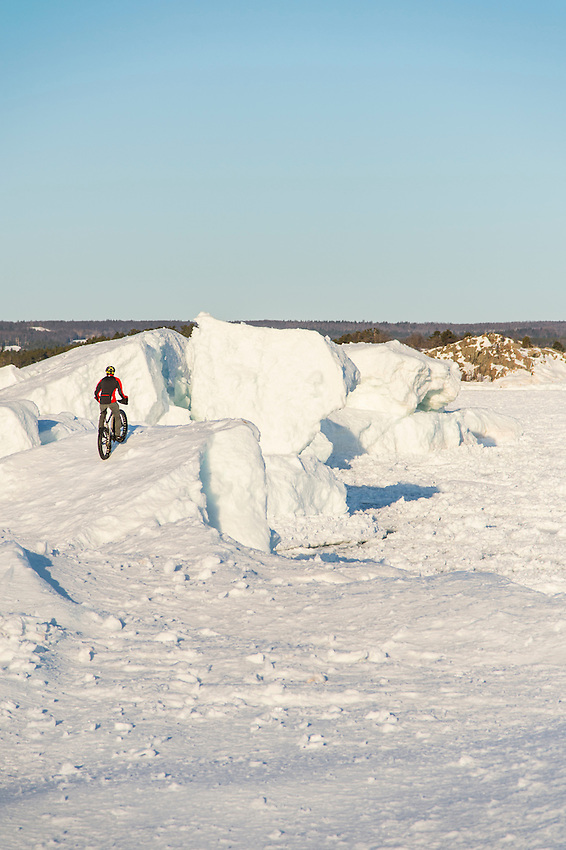 Ryan Labar rides the frozen shoreline of Lake Superior on a fat bike snow bike at Marquette, Michigan.