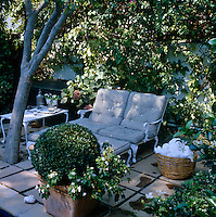 A pair of upholstered wrought-iron garden chaises are placed in the shade of a convenient tree on an impromptu terrace