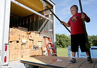 Corbin Smith, 8, moves fence posts out of the way Wednesday, June 24, 2020, before helping to unload a trailer of fireworks at the Fireworks City fireworks stand in Farmington. The stand, located next to the Fire Department will be selling fireworks through July 5 and offer a variety including individual family packs and classic favorites. Check out nwaonline.com/200625Daily/ and nwadg.com/photos for a photo gallery.<br /> (NWA Democrat-Gazette/David Gottschalk)