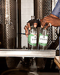 June 18, 2013. Chapel Hill, North Carolina<br />  Simon Hinson grabs bottles of TOPO Gin for corking.<br />  TOPO, Top of the Hill Distillery, the brainchild of owner Scott Maitland and Spirit Guide Esteban McMahan, is located in the old N&O Building on Franklin Street. Making gin, vodka and American whiskey from locally sourced wheat, they are one of the few distilleries bringing  organic liquor to ABC shelves around the state.