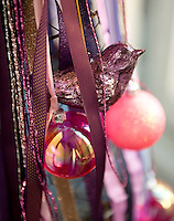 Detail of a robin Christmas decoration and baubles hanging from a Christmas tree made of ribbons