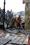 A firefighter pulling a hoseline into a collapsed building site