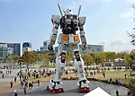 April 19, 2012, Tokyo, Japan - A flock of people is dwarfed by Gundam as the 18-meter-tall fighting robot from popular Japanese cartoon series returns to Odaiba, Tokyos waterfront area to celebrate the grand opening of the Diver City Tokyo Plaza, a new commercial complex housing the Gundam Front Tokyo run by Bandai Co. and other organizations, on Thursday, April 19, 2012. (Photo by Natsuki Sakai/AFLO)