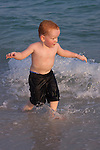 Redhead boy running in surf on beach