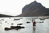 MAURITIUS, a mother and her child hunt for snails at low tide, Baie du Cap