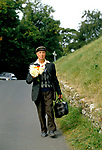 Country life 1990s. Albert Waring an elderly older  man walking to village cemetery with home grown flowers from his garden He will place them on his wife's grave. Eastleach Turville  Gloucestershire UK  1993.