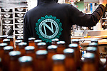 Bottled beer on the assembly line being capped and ready for boxing and shipping.  Ninkasi is a regional craft brewery making beers in the Northwest style. Their location in Eugene, Oregon affords regional access for their primary ingredients, which include: Water, Malt, Hops and Yeast. With the strong regional hop industry, and access to the McKenzie River, source of some of the cleanest water in the world, Ninkasi is well positioned for their goal of brewing high quality craft beers. The beer's namesake, Ninkasi, was the Sumerian goddess of fermentation.