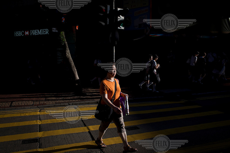 A woman crosses the road in front of an HSBC bank in a commercial area of central Hong Kong.