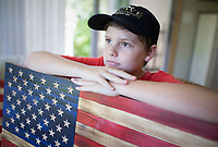 NWA Democrat-Gazette/CHARLIE KAIJO Jeremiah Lowe, 11, sits for a portrait holding an American flag he and his grandfather Don Lower (not pictured) created out of wood pieces, Monday, August 12, 2019 at Don's home in Bella Vista.<br /> <br /> Don Lowe and his grandson, Jeremiah Lowe, 11, turned their woodcrafting hobby into a business nine months ago after Don sold one of his wooden flags on Facebook within the first hour of posting it. It's a casual hobby he and his grandson share but they've sold 30 now in over four states, many to retired and active service members and emergency responders. He is working on a wooden flag he and his grandson will donate to the Bella Vista Fire Department.