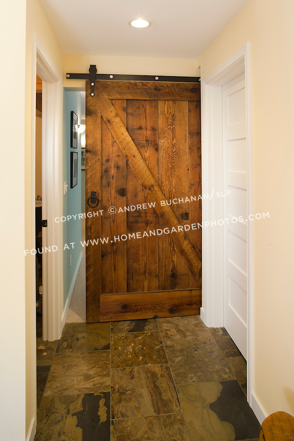 A sliding pocket door, made from reclaimed barn wood, separates the family room from the mudroom in this newly remodeled basement. This image is available through an alternate architectural stock image agency, Collinstock located here: http://www.collinstock.com
