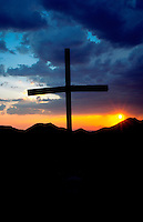 Sunset behind an old wood cross as summer thunderclouds darken the sky. Arizona.