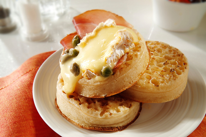 Melted goats cheese on buttered crumpets stock photos