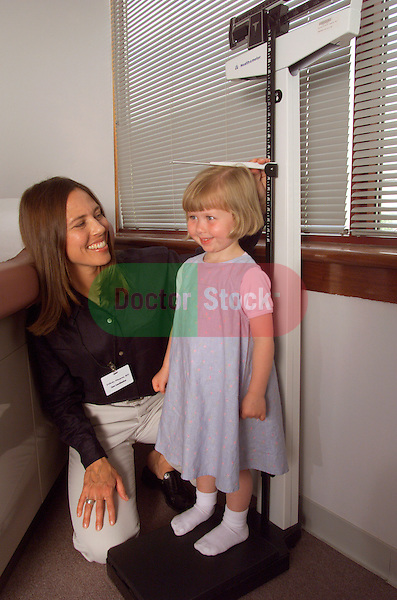 nurse in pediatrician's office measuring height of 3 year old girl