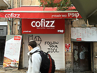 11. &quot;Cofizz: Follow your Idol&quot;. A young religious Jew walks by shuttered coffee shop and &quot;Follow Your Idol&quot; graffiti in a pedestrian walkway, West Jerusalem.<br />
