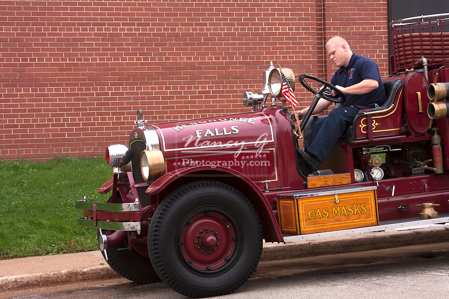 A Menomonee Falls Wisconsin antique 1926 Seagrave fire engine  being started by a department firefighter