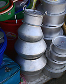 Stacked metal cooking pots somewhat precariously balanced found iin a marketplace in Bhutan.