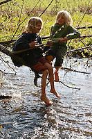 Jungen, Kind im Bach, Kinder einer 2. Grundschulklasse machen einen Schulausflug an einen Bach im Frühling und genießen das frische, kalte Wasser, klettern in überhängenden Zweigen und spritzen mit Wasser