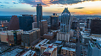 Aerial view of sunset falling on the downtown Austin skyline with JW Marriott Hotel, Frost Bank Tower and the Austonian residential skyscraper peaking out of the sky in Downtown Austin, Texas, USA.