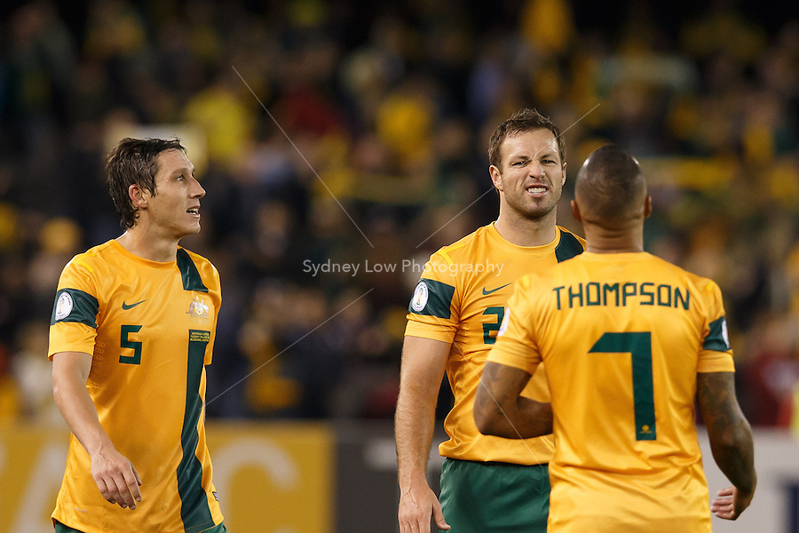 MELBOURNE, 11 JUNE 2013 - Mark MILLIGAN watches on as Archie THOMPSON and Lucas NEILL of Australia celebrate their win in a Round 4 FIFA 2014 World Cup qualifier match between Australia and Jordan at Etihad Stadium, Melbourne, Australia. Photo Sydney Low for Zumapress Inc. Please visit zumapress.com for editorial licensing. *This image is NOT FOR SALE via this web site.