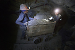 Two miners push a cart full of ore deep under Cerro Rico in Potosi, Bolivia. The mine produces silver and other metals.