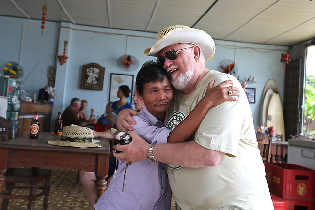 "Nguyen Tan Hoa, 55, embraces Marine Corps veteran Bill Taylor at Hoa's Place guesthouse on China Beach, south of Da Nang, Vietnam. Nguyen was 10-years-old when a Marine unit known as a Combined Action Platoon moved into his village, about 25 miles southwest of Da Nang. He soon began spending much of his time with the Americans and remembers it as the most profound experience of his life. ""Whatever they got, I got,"" he recalls. ""We shared the poncho together. We shared the cigarette together. We shared everything."" Nguyen occasionally hosts groups of returning veterans for lunch at the guesthouse. Taylor, 65, of Dyer, Ind., served with 1st Battalion, 3rd Marine Regiment from 1967 to 1968. This was his first time back in Vietnam since the war. ""I've already lost it a couple of times,"" he said. ""But it's been a refreshing feeling. I'm here with my brothers."" April 27, 2012."
