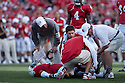 26 September 2009: Nebraska Head Coach Bo Pelini checking on injured player Rickey Thenarse. Thenarse was injured in the 1st quarter during a kick off to Louisiana-Lafayette at Memorial Stadium, Lincoln, Nebraska. Nebraska defeats Louisiana Lafayette 55 to 0.