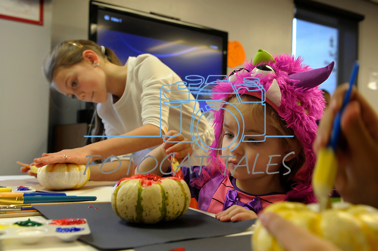 Abby Marschner, 10, left, and Annalise Schumacher,3,  create some Halloween art at the Carson City Library Monday, Oct. 27, 2014. As part of the library's Halloween festivities, dozens of children decorated pumpkins or gourds and took part in a costume contest.