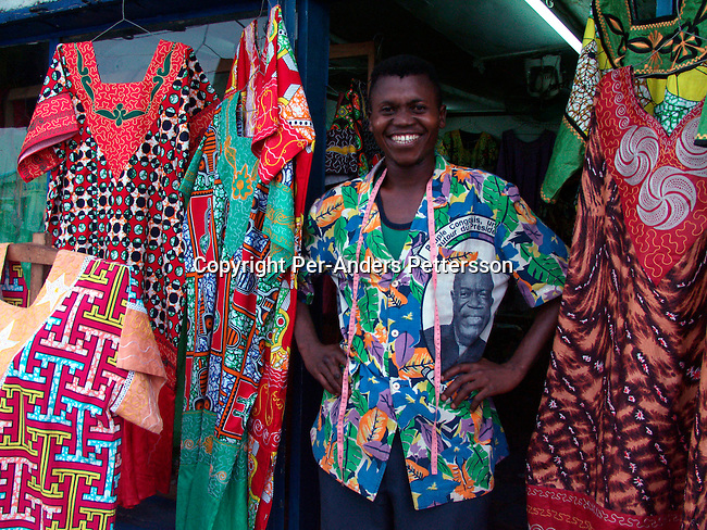 dicocon00172.Congo.  Kinshasa.  Business, retail, traditional clothes and dresses. Sylla Amara, a tailor outside his shop (called Mandino) with his work on February 28, 2002 in a busy street in central Kinshasa, Congo.  The shirts are typical Congolese, but also makes West African shirts for clients. Especially women come to buy his clothes and his clientele includes people from Zimbabwe, Mali and Togo..©Per-Anders Pettersson/iAfrika Photos