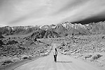 Woman walking down Movie Road from Alabama Hills in this black and white landscape shot.