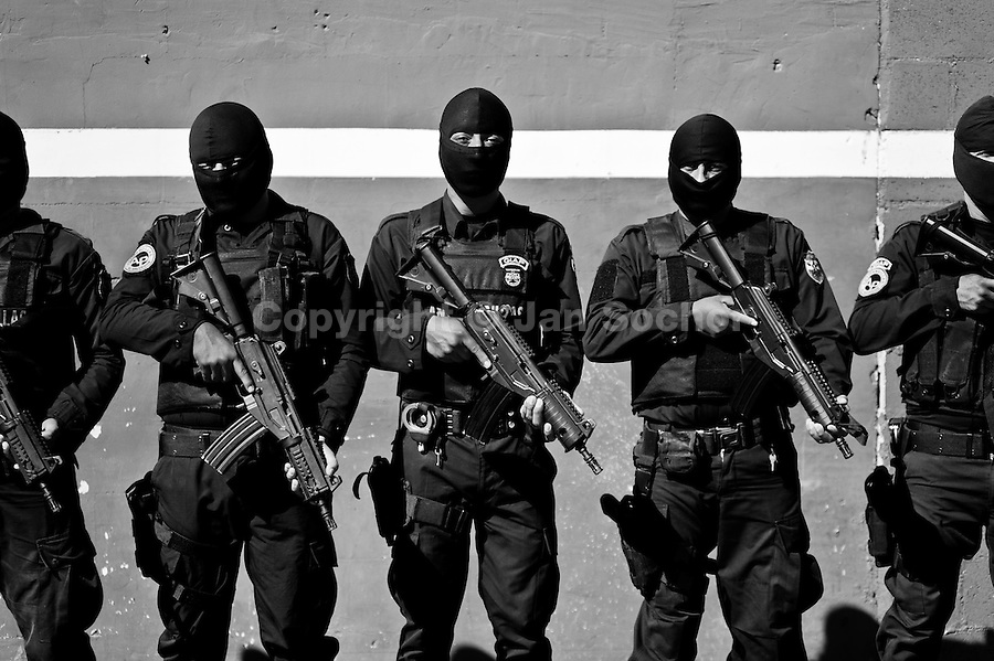 Salvadorean policemen, members of the specialized anti-gang unit (Unidad Antipandillas), receive an order on the police base before leaving for an operation in San Salvador, El Salvador, 19 December 2013. During the last two decades, Central America has become the deadliest region in the world that is not at war. According to the UN statistics, more people per capita were killed in El Salvador than in Iraq, in recent years. Due to the criminal activities of Mara Salvatrucha (MS-13) and 18th Street Gang (M-18), the two major street gangs in El Salvador, the country has fallen into the spiral of fear, violence and death. Thousands of Mara gang members, both on the streets or in the overcrowded prisons, organize and run extortions, distribution of drugs and kidnappings. Tattooed armed young men, mainly from the poorest neighborhoods, fight unmerciful turf battles with their coevals from the rival gang, balancing between life and death every day. Twenty years after the devastating civil war, a social war has paralyzed the nation of El Salvador.