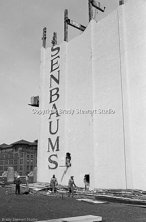 Pittsburgh PA:  View of the building demolition of one of downtown Pittsburgh's grand old department stores, Rosenbaums. Men working on the roof and preparing to bring down the Rosenbaums sign. Located at Penn Avenue and Sixth Street in Pittsburgh, the store closed in 1960 and taken down in 1963 to make way for the Sixth Avenue garage.  The demolition work was completed by D&H Building Wreckers.