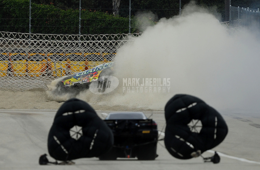 Nov. 11, 2011; Pomona, CA, USA; NHRA top alcohol funny car driver Brian Smith crashes into the sand trap and net containment system after his parachutes failed to deploy during qualifying at the Auto Club Finals at Auto Club Raceway at Pomona. Mandatory Credit: Mark J. Rebilas-.