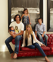 Nacho Figueras and his family pose on the large red-leather Chesterfield sofa in the living room