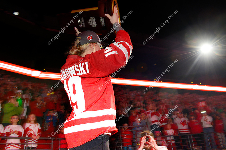 Annie Pankowski holds the championship trophy while taking the stage during the NCAA championship awards ceremony on Monday, 3/25/19, at the Kohl Center in Madison, Wisconsin. Pankowski scored three goals during the Frozen Four as the Badgers took the championship.