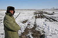 A shepherd is tending his flock to the frozen fields of Heilongjiang province, China, on February 27, 2006. Photo by Lucas Schifres/Pictobank