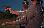 An instructor works to familiarize a student with handgun safety at a shooting range in Texas.