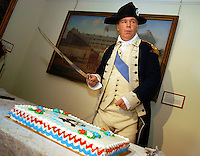 TRENTON, NJ - FEBRUARY 16: David Emerson, portraying General George Washington, uses his sword to cut his birthday cake during a President's Day celebration at the Old Barracks Museum February 16, 2004 in Trenton, New Jersey. The birthday celebration featured re-enactors and a birthday cake which was cut by Gen. Washington as part of the Museum's President's Day festivities. (Photo by William Thomas Cain/Getty Images)