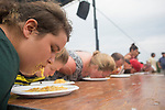Denise McDonough, front, participates in the pawpaw-eating contest with others at the Pawpaw Festival on Sept. 17, 2016.