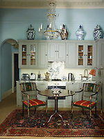 The kitchen has been furnished with antiques that lend a distinctive mood. Large oriental jars sit atop the cupboards and a crystal chandelier adds an elegant touch.