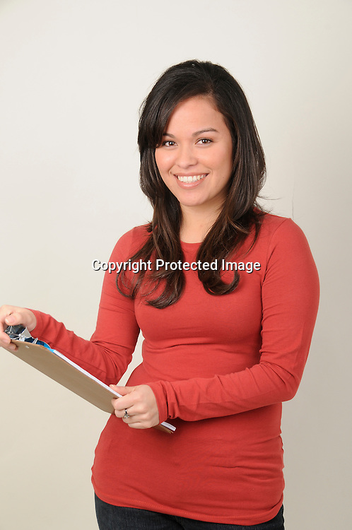 Hispanic woman at business holding clipboard
