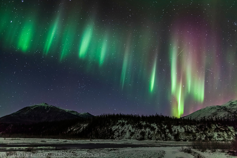 Colorful green and violet aurora borealis and starry night sky over the Koyukuk river in Alaska's Brooks Range.