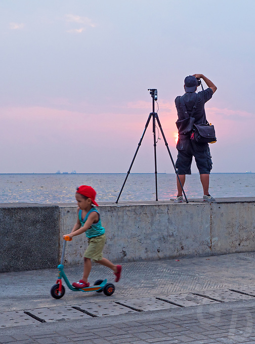 General life and environs in the Malate, Manila area and Manila Bay, Philippines. Sunset, Photographer at sunset. Child playing.