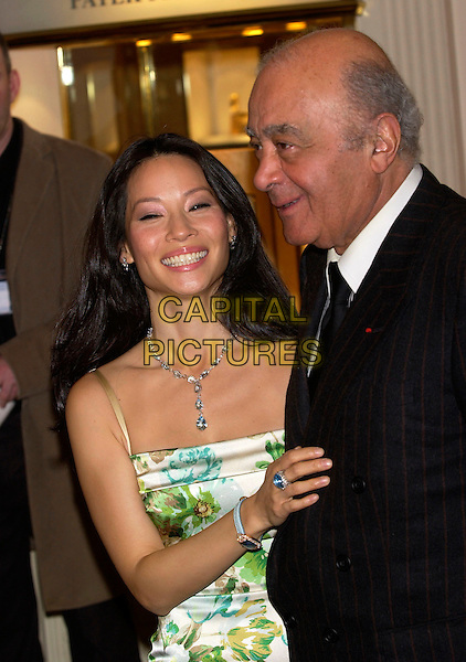 LUCY LIU & MOHAMED AL FAYED.Opening of the Harrods January Sale, Harrods, Knightsbridge, London, January 3rd 2005..half length green blue brown floral flower print patterned dress diamond necklace ring jewellery smiling.Ref: PL.www.capitalpictures.com.sales@capitalpictures.com.©Capital Pictures.
