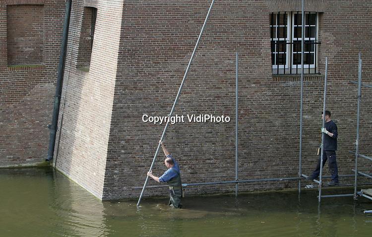 Foto: VidiPhoto..DE STEEG - Steigerbouwers zijn donderdag aan het werk in de gracht aan de buitenzijde van Kasteel Middachten in De Steeg bij Arnhem. Alles wordt in gereedgeheid gebracht voor de tweede fase van een ingrijpend onderhoud van het metsel- en voegwerk aan de voor- en westgevel van het kasteel. Vorig jaar zijn met de eerste fase de noord- en zuidzijde en de brug gerestaureerd. Het tweede deel van deze reatauratie begint over enkele weken. Het project wordt uitgevoerd door Hoffman BV uit Beltrum in opdracht van Landgoed Middachten BV. De totale kosten bedragen 7 ton.