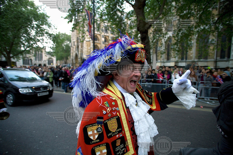 A town crier performs outside Westminster Abbey, London as people prepare to celebrate on the day before the Royal Wedding between Britain's Prince William and Kate Middleton.