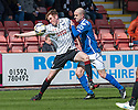 Pars' Lewis Martin and Stranraer's Jamie Longworth challenge for the ball.