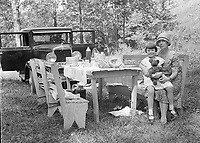 Woman and little girl with Teddy Bear at a picnic table next to their car, circa 1930's.   (photo: www.bcpix.com)