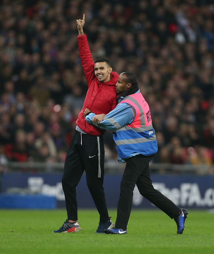 A pitch invader is escorted off the pitch<br /> <br /> Photographer Rob Newell/CameraSport<br /> <br /> The Wayne Rooney Foundation International - England v United States - Thursday 15th November 2018 - Wembley Stadium - London<br /> <br /> World Copyright © 2018 CameraSport. All rights reserved. 43 Linden Ave. Countesthorpe. Leicester. England. LE8 5PG - Tel: +44 (0) 116 277 4147 - admin@camerasport.com - www.camerasport.com