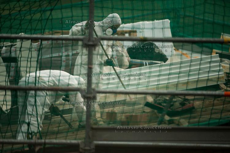 Milano, operai con tuta e maschere rimuovono lastre di amianto da un tetto.<br /> Milan, workers with overalls and masks remove asbestos sheets from a roof.